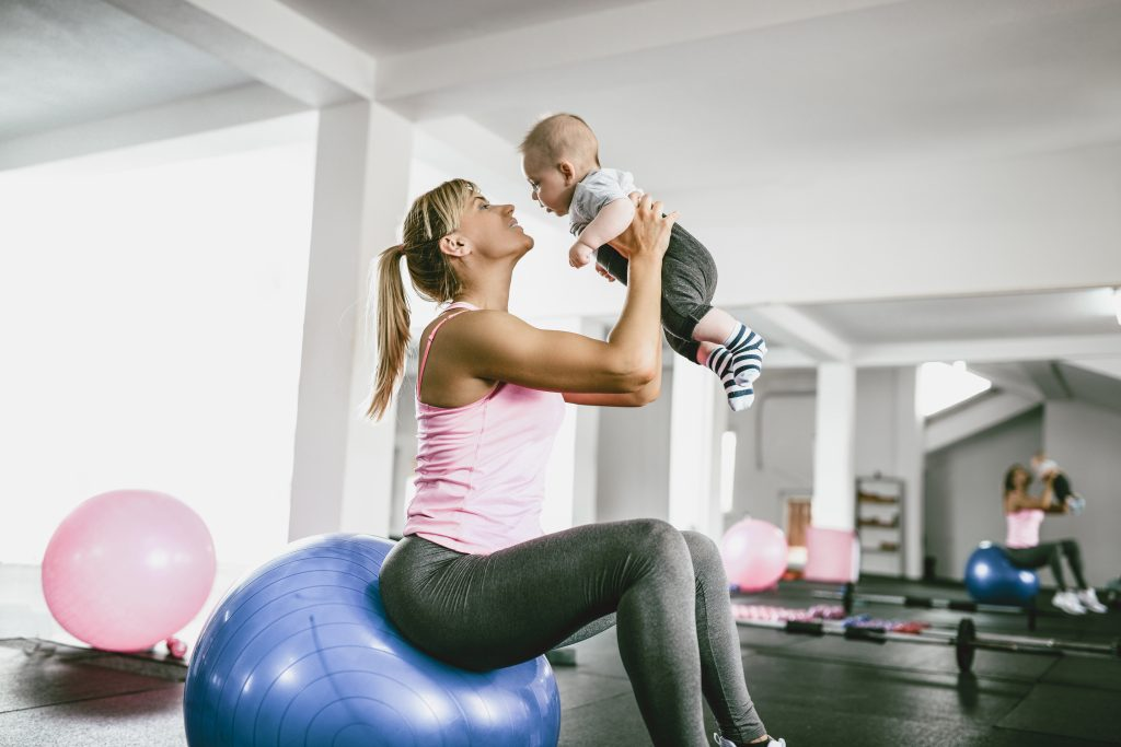Athlete Mother Playing With Baby While Resting From Workout In Gym