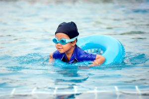 cute child swimming in pool with swim ring