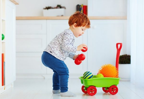Cute-redhead-toddler-baby-collecting-different-balls-into-toy-pushcart