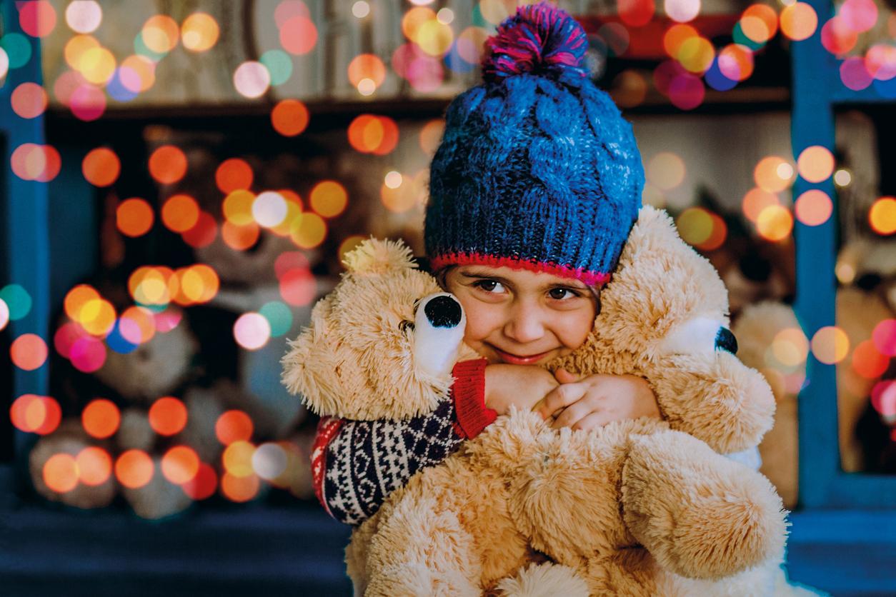Girl with a teddy bear near lights